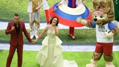 Роби Уилямс пее на откриващата церемония заедно със сопраното Аида Гарифулина. До тях е талисманът на турнира Забивака
