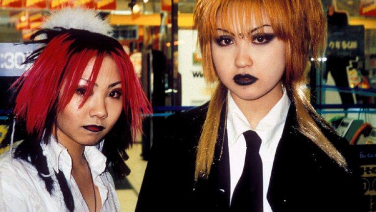 """Момичета, пременени в стил """"Гангуро"""". Това е мода на гримиране от 90-те години, която предполага носенето на почти карнавален грим посред бял ден и много японски момичета са луди по тази тенденция. За основа се ползва възможно най-тъмно на цвят мазило и отгоре се оцветява. Носи се без повод."""