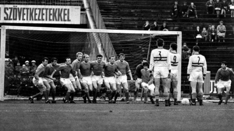 """6 юни 1965 г. - Европейски приключения. Флориан Алберт и Дежо Новак от Ференцварош мислят как да преодолеят стена от целия тим на Юнайтед в реванша  от полуфиналите на Купата на панаирните градове. """"Червените дяволи"""" бият с 3:2 у дома, но губят с 0:1 в Унгария. Тогава правило за голове на чужд терен няма, та се налага 10 дни по-късно Юнайтед пак да пътува за Будапеща в трети мач. И отново губи. Европейската слава ще почака. На снимката, от ляво на дясно: Джон Конъли, Шей Бренън, Ноби Стайлс, Денис Лоу, Боби Чарлтън, Били Фоулкс, Пат Креранд, Дейвид Херд, Джордж Бест, вратарят Пат Дън и Тони Дън."""