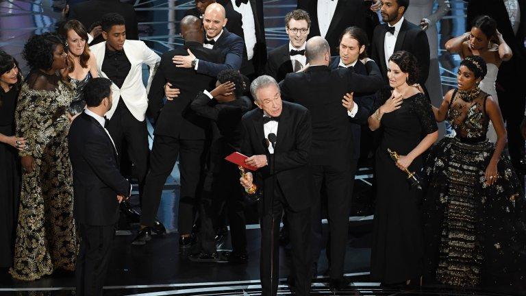 """Хайде, пак! Кой печели наградата за най-добър филм? Сагата със сгрешения плик до момента е най-големият гаф на организаторите на наградите """"Оскар"""". Победителят в категорията най-добър филм за 2017-та трябваше да обявят актьорите Уорън Бийти и Фей Дънауей, но вместо плика с филма победител, на тях е връчен плик с името на Ема Стоун, която по-рано е взела статуетката за най-добра главна женска роля в """"Ла Ла Ленд"""". Когато двамата отварят плика, по лицето на Уорън Бийти се чете объркване, а Фей Дънауей обявява """"Ла Ла Ленд"""" за най-добър филм. Минути по-късно грешката е поправена на сцената и продуцентите на """"Ла Ла Ленд"""" дават """"Оскар""""-а на реалния победител - """"Лунна светлина"""" (Moonlight)."""