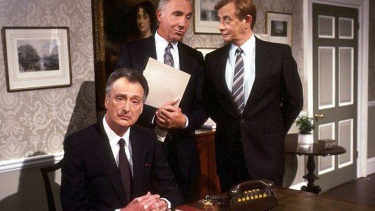"""Yes, Minister / Yes, Prime Minister / """"Да, г-н министър"""" / """"Да, г-н премиер"""" Малко преди британския House Of Cards да се появи по екраните, един друг политически сериал чертае """"истината"""" за това, което се случва по коридорите на Уестминстър - """"Да, г-н министър"""". Комедийният сериал е една от най-добрите политически сатири правени въобще някога, като самата Маргарет Тачър се шегува, че сценаристите на шоуто имат свой човек във властта, който им дава информация какво и как се случва в управлението на Великобритания.  В основата на историята тук е Джим Хакър - млад политик, на който е обещано да стане министър. Политическите игри обаче го пращат на мястото, известно като """"гробището за политици"""" - Министерството на държавната администрация. Там той трябва да работи с личния си секретар Бърнард и с манипулативния и хитър главен секретар на министерството - сър Хъмфри, който реално управлява цялата държавна администрация. Това, което следва, са много шеги, комични и неудобни ситуации и игра на надцакване между министър и главен секретар.  В по-късните сезони на шоуто - Джим Хакър успява по случайност да стане премиер и да се сблъска вече с още по-големи и нелепи проблеми от политическия живот на Великобритания. Едно е сигурно - Yes, Minister и до днес остава един от най-гениалните британски комедийни сериали."""