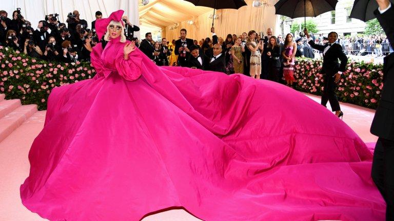 """Лейди Гага   Известно време Лейди Гага беше загърбила екстравагантния си имидж, особено около представянето на филмовия си дебют - """"Роди се звезда"""". На Мет Гала обаче тя се завърна към добре познатия шокиращ имидж.  Певицата смени общо четири тоалета като в един момент остана само по черно бельо и мрежести чорапи, а зад нея имаше количка, натоварена с шампанско. Сред другите й аксесоари бяха чадър, огромни слънчеви очила и огромен бутафорен телефон."""