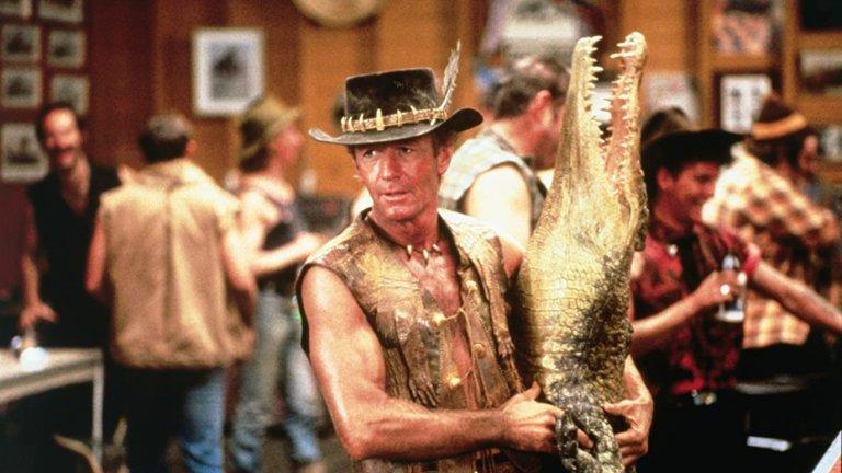"""Crocodile Dundee / """"Дънди крокодила""""  Тук вече говорим за величие, което нарежда филма в категорията """"национално богатство"""" на Австралия, наред """"Лудия Макс"""", разбира се. Едва ли ще е преувеличено, ако кажем, че именно историята за Дънди е в основата на затвърждаването на всеки един възможен стереотип за Австралия. Филмът разказва за коравия Майкъл Дънди, който живее в австралийската пустош, а основното му занимание е да лови крокодили с голи ръце и да се напива до припадък. Всичко обаче се променя, когато се среща с една американска журналистка и заминава с нея за Ню Йорк."""