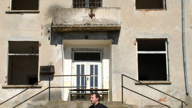 Бившите лагерници са заковали черен дървен кръст върху прозореца на тази сграда от външната страна: силен символ, но недостатъчен жест за памет