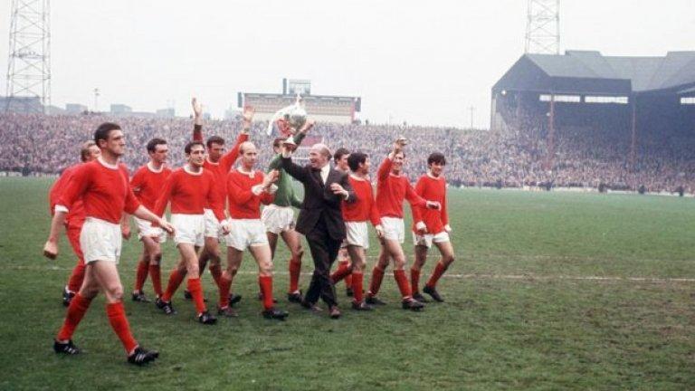 """13 май 1967 г. - Трофеят се връща у дома. И Юнайтед е шампион, след като оправя формата си като гост. Бъзби носи трофея из терена на """"Олд Трафорд"""", а играчите от ляво на дясно са: Денис Лоу, Били Фоулкс, Джон Астън, Шей Бренън, Дейвид Садлър, Боби Чарлтън, Алекс Степни, Джими Райън, Тони Дън, Пат Креранд и Бест."""