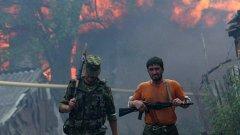 Южноосетински доброволци патрулират около горящото си село по време на войнaта между Русия и Грузия през 2008 г.