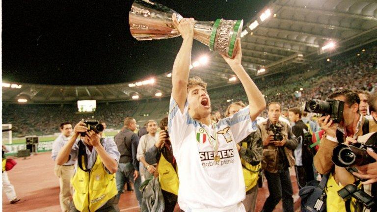 """Лацио 1999/00 След разочарованието дойде и голямата радост от историческия дубъл. Ювентус водеше с девет точки осем кръга преди края, но допусна загуба от шампиона Милан с 0:2, преди да бъде победен с 1:0 от бъдещия шампион Лацио на """"Деле Алпи"""". Тимът на Карло Анчелоти се възстанови с три поредни победи, но загуби с 0:2 от Верона, а разликата се стопи до само две точки. И двата отбора спечелиха мачовете си от 34-тия кръг, когато дойде и един от най-скандалните завършеци на сезона в историята на Серия А. Лацио спечели с 3:0 на """"Олимпико"""" срещу Реджина, но по-интересното се случваше в Перуджа, където Ювентус гостуваше. Двубоят започна при перфектно време, но изведнъж на стадиона се изсипа порой, придружен с гръмотевична буря. Съдията Пиерлуиджи Колина забави началото на втората част с час, докато според някои двубоят е трябвало да бъде отменен и да се преиграе в друг ден. В Рим всички очакваха новини от Перуджа, а Юве загуби с 0:1 след гол на защитника Алесандро Калори (защитник, името на когото започва с """"К"""", вкарва гол – да ви звучи познато? - б.а.). В крайна сметка, Лацио спечели титлата със само точка преднина пред """"старата госпожа""""."""