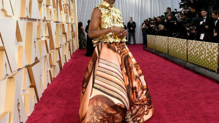 Били Портър   Накъде без Били Портър, когато говорим за рокли? Тук той е с рокля на Сам Рател, специално изработена за него и вдъхновена от двореца Кенсингтън. Горната част е от пера, направени от чисто 24-каратово злато.