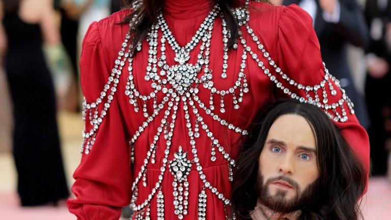 """Джаред Лето   Лето също се заигра на тема """"многоликия"""" и се появи с правдоподобно копие на собствената си глава в едната си ръка. Репликата беше много сполучлива и отвлече вниманието от сатенения му костюм на Gucci, украсен с нанизи от кристал. Актьорът обаче каза, че носи копие на главата си като ирония към славата си и медийното внимание към него."""