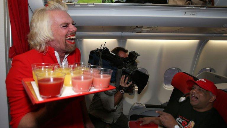 Собственикът на Virgin Atlantic Ричард Брансън, дегизиран като стюардеса, обслужва пътниците в AirAsia, след като се хваща на бас с Тони Фернандес, че неговият отбор във Формула 1 ще победи отбора на малайзиеца.