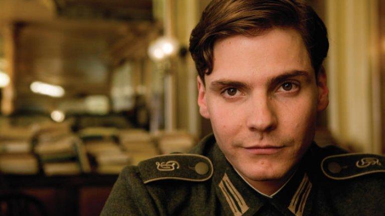 """""""Гадни копилета"""" (Inglorious Basterds)  Този филм на Тарантино никога няма да ни омръзне и винаги откриваме по нещо ново, което преди не сме забелязали в него. Тук режисьорът прекроява историята и зрелищно убива Хитлер в едно парижко кино, а филмът е изпълнен с точно толкова кръв, насилие и не особено коректен политически хумор, колкото ни харесва.   Ролята на Брюл е сравнително второстепенна, но запомняща се. Той е Фредерик Цолер, който въпреки младостта си вече е герой на Германия от Втората световна война и на него се посвещават пропагандни филми. Нещата се заплитат, когато Цолер започва да си пада по една привлекателна руса французойка, а жестокостта му на екрана е доста шокираща.   Можете да гледате """"Гадни копилета"""" в платформата на Netflix."""