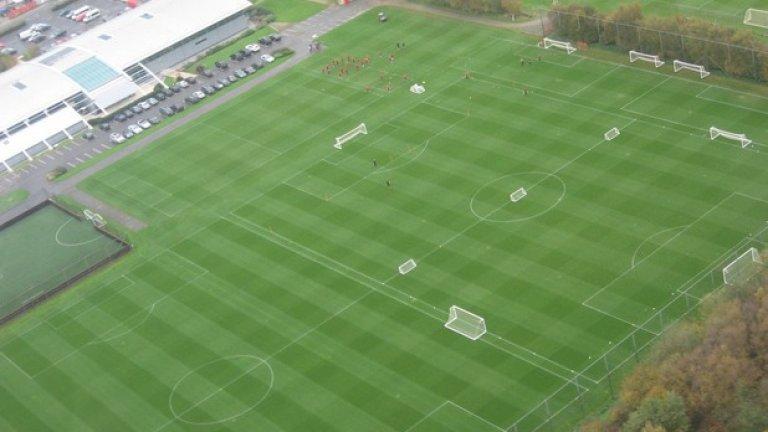 Освен като AON Training Complex по очевидни спонсорски причини, базата е известна още като The Trafford Training Centre и Carrington.