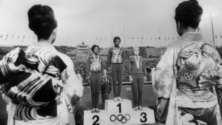 """10. Токио 1964: Не може да се вярва на половите тестове Ева Клобуковска, полска спринтьорка, печели злато на 4х100 м и бронз на 100 м (жената върху стълбичката за трето място на снимката). През 1967 година обаче  Клобуковска """"се проваля"""" на половите тестове и всичките й медали са отнети. Години по-късно, когато Клобуковкса ражда сина си обаче, всички разбират, че тези тестове не са напълно 100-процентови, а полякинята има хромозома в повече."""
