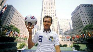 """Франц Бекенбауер се снима пред Рокфелер Сентър в Ню Йорк през 1977 г., когато подписва с Космос. Германската легенда печели за втори път """"Златната топка"""" само година по-рано. Кайзерът поема щафетата от Пеле за лице на супертима Космос и футбола в Щатите."""