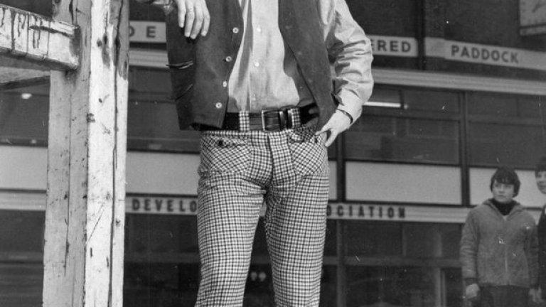 """18 декември 1965 г. - Гуру в модата. Бест позира пред """"Олд Трафорд"""" преди Коледа, като вече е наясно, че статутът му на звезда на терена е съпроводен с огромна популярност извън него. Юнайтед се е надигнал от разгрома от Тотнъм - 7 победи в 9 мача, като Бест помага с 6 гола в този период. Но за съжаление на него и клуба, на 60 километра от тях Ливърпул прави невероятен сезон и още през ноември изглежда непобедим. Мат Бъзби обръща цялото си внимание към Купата на европейските шампиони."""