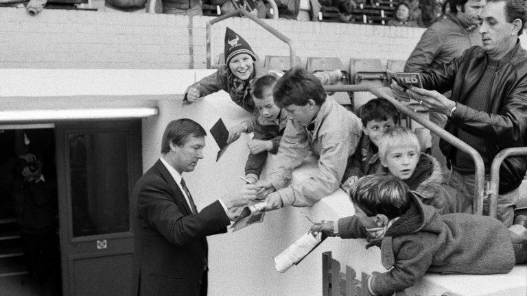 """Алекс Фъргюсън (все още без """"сър"""" пред името си) дава автографи на малки фенове на Оксфорд Юнайтед на """"Манор Граунд"""" преди първия си мач начело на Манчестър Юнайтед през 1986 г."""