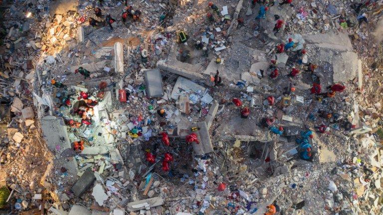 Птичи поглед към една останките от една от срутените сгради, осеяна със спасители.